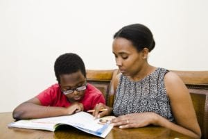 Black mother reads with her young son at home.